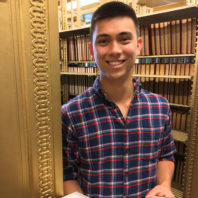 ARCS Scholar Benjamin Lee posing with a book open in the library
