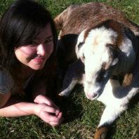 ARCS Scholar Jenna Murray posing with goat on green grass