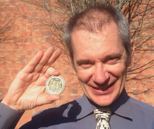 """Thomas Gazzola with the winning """"Nautilodestone"""" coin from the MIT Mystery Hunt. Photo courtesy WSU Vancouver."""