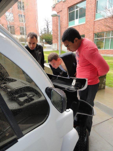 SEL's Shawn Greeman and Eddie Schweitzer examine the electric car recently donated to WSU with Javier Guerrero-Sedeno, a WSU instructor in renewable energy.