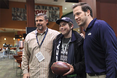 Spencer meets former NFL players and Seahawks Radio Network broadcasters Dave Wyman (left) and Craig Terrill.
